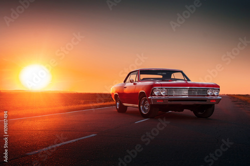Poster Vintage cars Retro red car standing on asphalt road at sunset