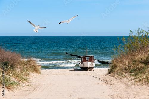 Spoed Foto op Canvas Noordzee Strandaufgang mit Fischerbot und Möwen
