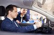 people and technology concept - salesman showing new car to male