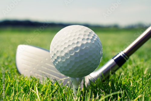 Golf club and ball on tee in grass - 109823207