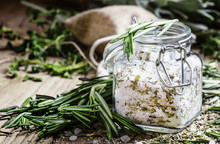 Sea Salt With Dried Rosemary In A Glass Jar, Vintage Wooden Back
