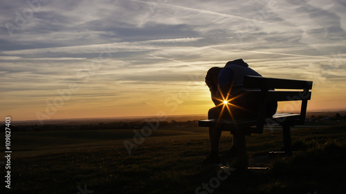 Sad unhappy silhouette man sitting with his head in his hands on a bench at suns Fototapeta