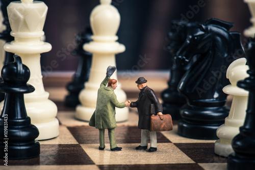 Photo チェス盤の上で握手をしているミニチュアのビジネスマン