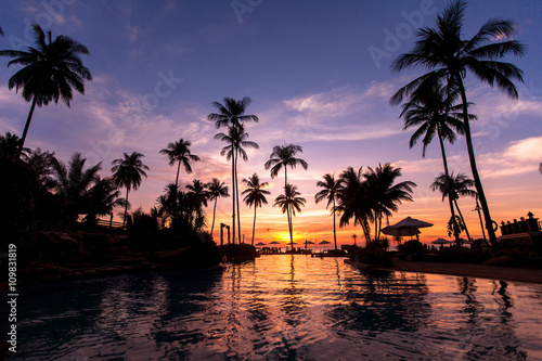 Beautiful twilight on the beach with palm trees reflected in pool.
