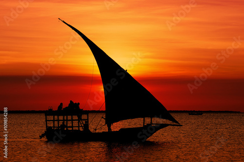 La pose en embrasure Rouge mauve Fishermen Dhow Boat coming back home at sunset from a long day in the sea.