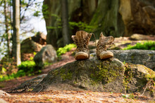 Well-worn Hiking Boots, Unlaced And Muddy On The Forest Floor. Tourism Concept.