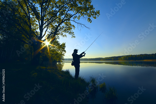 Obraz silhouette of a fisherman with a fishing rod on the shore of the lake, the river in the morning. The rays of the rising sun filtering through the tree leaves
