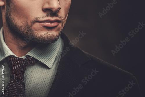 Obraz na plátne Serious well-dressed hispanic man posing on dark background.