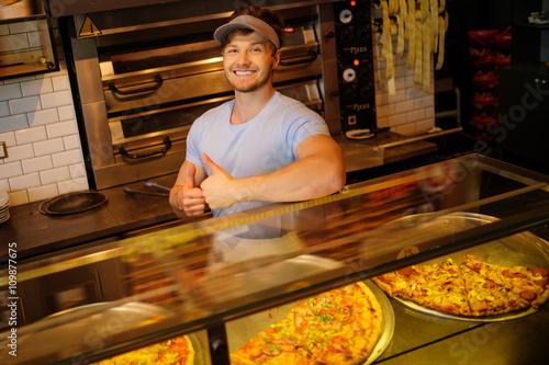Foto op Canvas Pizzeria Handsome pizzaiolo standing at kitchen in pizzeria.