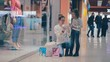 Mother shows her daughter a pesent, just baught in mall while shopping. HD.