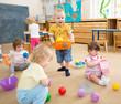 kids playing with balls in kindergarten room