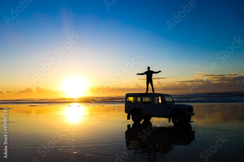 Photo  Sunrise on the beach with a land rover defender on Fraser Island Australia