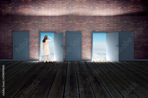 Fotografía  Composite image of rear view of young businesswoman looking away