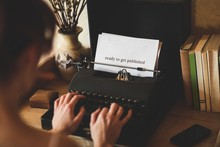 Ready To Get Published Against Young Woman Using Typewriter
