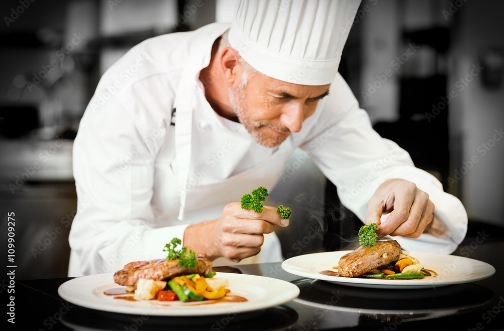 Fototapety, obrazy: Concentrated male chef garnishing food in kitchen