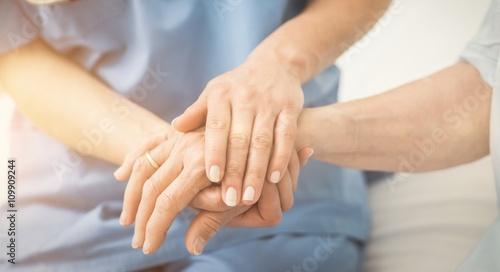 Fotografia  Composite image of nurse holding patient hand