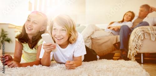 Fotografía  Siblings lying on the floor watching tv