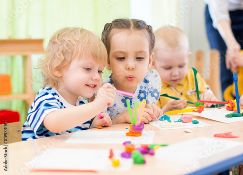 Obraz happy kids doing arts and crafts in day care centre - fototapety do salonu