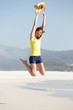Excited young woman jumping on the beach