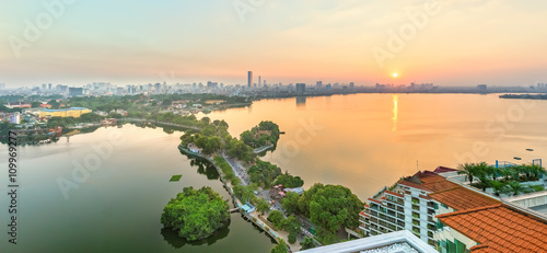 Hanoi, Vietnam, September 28, 2015: Panorama West lake sunset when sun go down horizon where skyscrapers, still lake, green path through small island creates beauty idyllic watching in Hanoi, Vietnam
