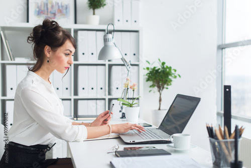 Female office worker using laptop at her workplace, browsing information, surfing the internet, side view portrait Canvas-taulu