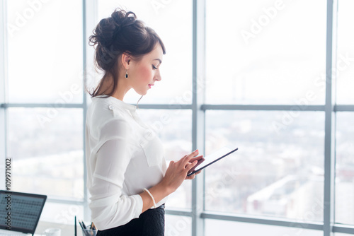 Valokuva  Portrait of an office manager holding her tablet, typing, using wi-fi internet and applications touching the pda screen
