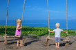 Caucasian little sibling - girl and boy have fun together on rope swing, look at black sand beach, sea surf on tropical island. Travel lifestyle, people activity on summer family vacation with child.