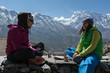 two girls enjoying tea or coffee on Annapurna trek circuit, Nepa