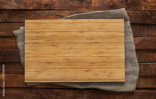 Cutting board on brown wooden table, top view