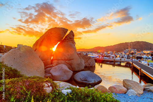 Photo  A sunset over lake with a port in the background