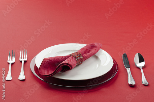 Photo  table setting with utensils, plate and red cloth.