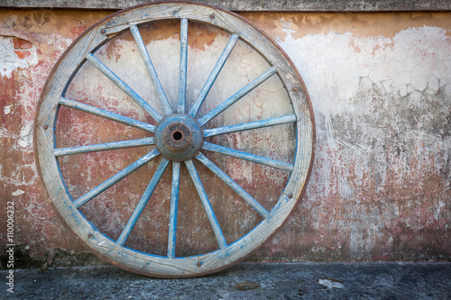 Fotografía  Old ironed, blue wagon or carriage wheel