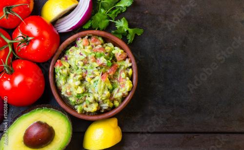 Fotografía  Guacamole and ingredients - avocado, tomatoes, onion, cilantro dark background