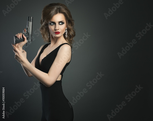 Sexy beauty young woman with gun on a dark bg portrait Canvas Print