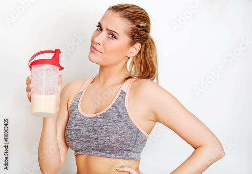 Fotografia  Młoda sporty kobieta z proteinową potrząśnięcie butelką