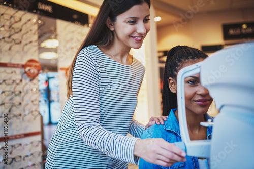 Fotografía  Pretty optometrist helps woman take her eye exam