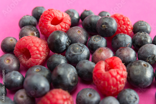 Canvas Prints Fruits Raspberries and blueberries blue background