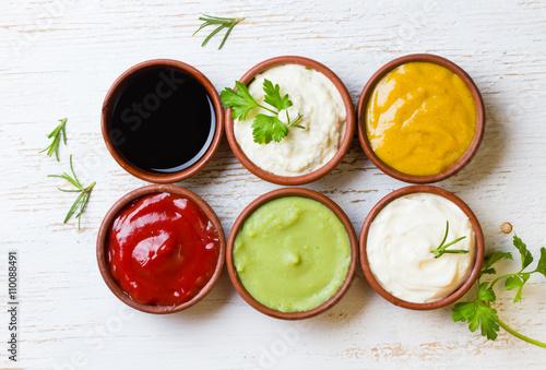 Photo  Sauces ketchup, mustar, mayonnaise, wasabi, soy sauce in clay bowls