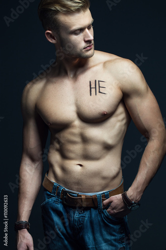 Poster Akt Handsome muscular male model with intense glance posing over grey background. Perfect body with the inscription