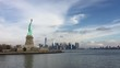 Beautiful blue cloud sky and city skyline behind bright green statue of liberty on reflective Hudson waters.