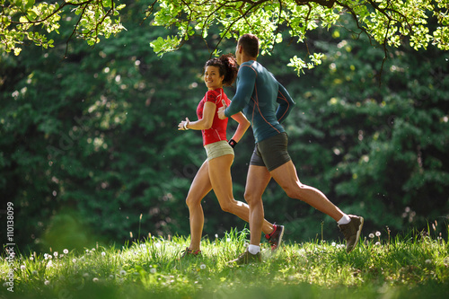 Papiers peints Jogging Young couple jogging at the woods.Green environment.