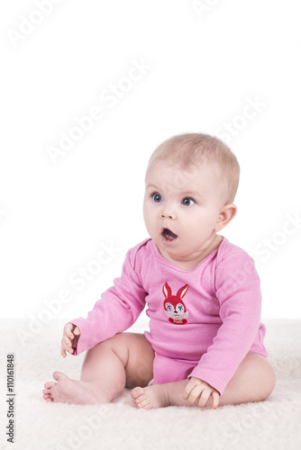 267ce8970 cute little baby in pink bodysuit sitting on a blanket and looking ...