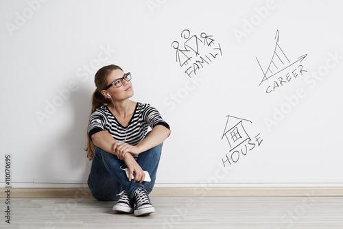 Foto  Junge durchdachte Frau, die über ihre Zukunft, die Planung der erfolgreichen Karriere, der großen Familie und der neuen Wohnung träumt