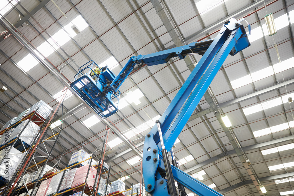 Fototapety, obrazy: Moving stock in a warehouse with a cherry picker, low angle
