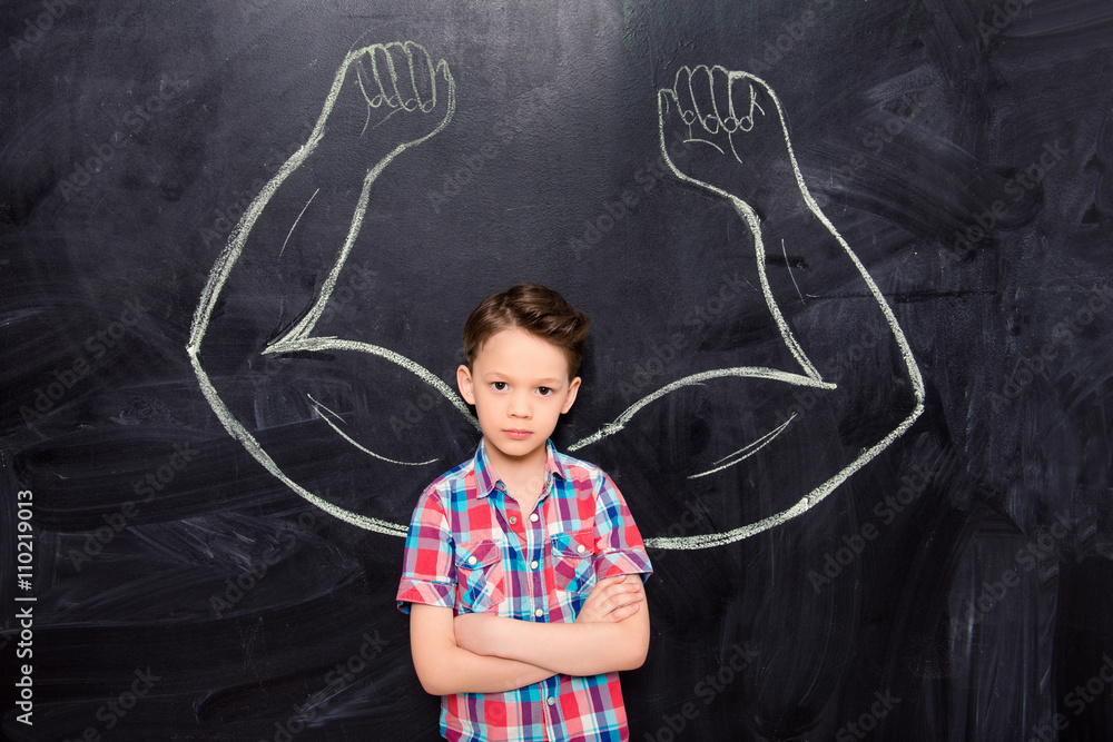 Photo  Little boy on backgroung of blackboard with drawn muscles