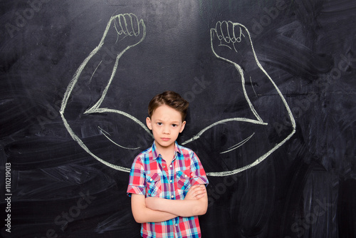 Little boy on backgroung of blackboard with drawn muscles Canvas Print