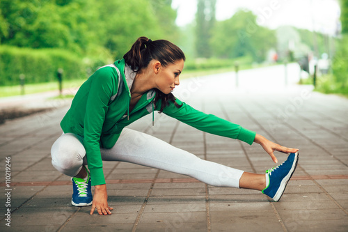 Young fitness woman runner stretching legs before run - 110219246