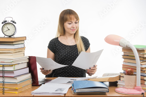 Photo  Joyful girl behind a desk littered with books, looking at the paper in his hands
