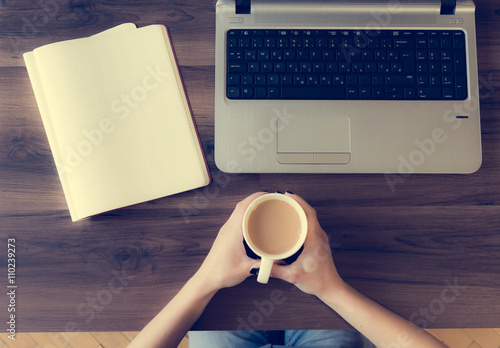 Office desk with person holding a cup while working. Poster