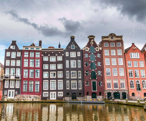 Spoed Fotobehang Amsterdam Moody clouds hang over houses built in the 17th century along the canals of Amsterdam.